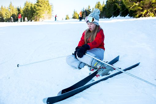 Teenage ski girl holding her knee in pain after accident on ski slope.